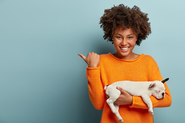 Horizontal shot of pleased Afro woman points away at free space, shows direction to pet store, bought pedigree puppy, has pleasant smile on face models over blue background. Love between dog and owner