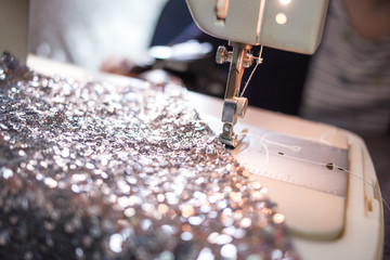 Close-up photo of sewing machine with shiny piece of fabric. Prom dress preparation. Fashion design concept