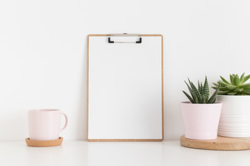 Wooden clipboard mockup with various types of succulents and a cup on a white table.
