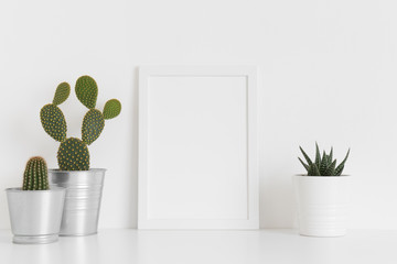 White frame mockup with various types of cactus and a succulent plant on a white table. Portrait orientation.