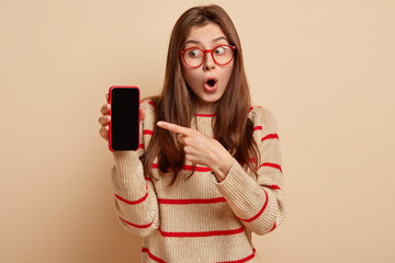 Surprised European young woman opens mouth from wonder, points at mobile phone with blank screen for content template, design, wears beige jumper with red stripes, isolated over brown background