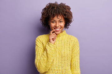 Headshot of glad attractive female looks at camera, poses for making photo, smiles broadly, keeps fore finger near mouth, wears knitted warm sweater, laughs at something positive, isolated on violet