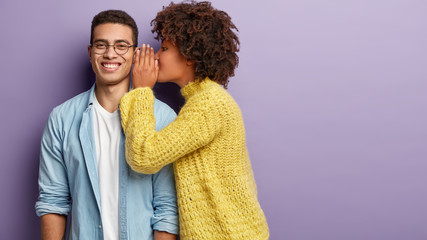 Afro American female whispers secret to boyfriend who has cheerful expression, gossip together, wear casual clothes, stands against purple background with blank space. Diverse couple indoor. Wall mural