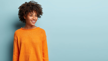 Image of dreamy woman with crisp hair looks pensively aside, has gentle smile on face, wears orange jumper, imagines something pleasant, models over blue background, blank space for promotion