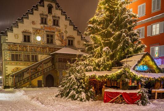 romantischer, idyllischer Winkel in der tief verschneiten Altstadt von Lindau mit schneebedecktem Christbaum, Weihnachtsbaum, altem Rathaus und Budenzauber