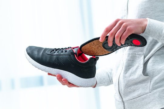 Orthopedic insoles for sports shoes. Treatment and prevention of flat feet and orthopedic foot diseases. Foot care, feet comfort. Health care, wearing comfortable shoes