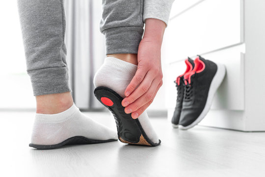 Sports woman fitting orthopedic insoles. Treatment and prevention of flat feet and foot orthopedic diseases. Foot care, feet comfort. Health care. Wearing sports comfortable shoes