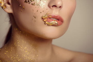 Part of the face lips. Golden mask on the cheeks lips and neck