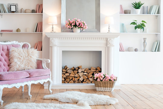 Modern light interior with fireplace, spring flowers and cozy pink sofa