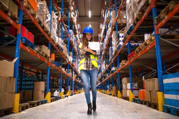 Portrait of confident female worker walking through distribution warehouse. Smiling woman holding checklist.