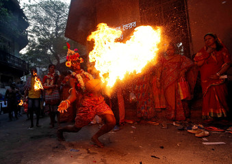 A man throws fire towards the gate of a temple as part of a ritual ending a religious procession held to mark the Gajan festival in Kolkata
