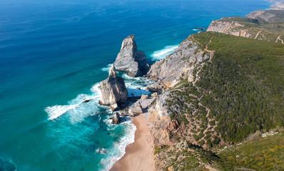 Aerial view from a sandy wild beach with amazing rocks. Ursa Beach at atlantic coast, Portugal