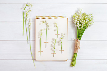 Herbarium with lilies of the valley and flower bouquet on white wooden background