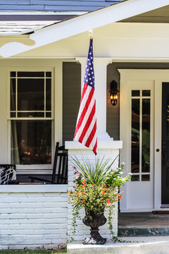Closeup of entrance to cottage house with beautiful flowers in a pot and American flag by porch
