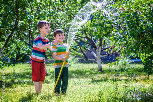 Cute Little Boy Watering Plants With Hose In The Garden