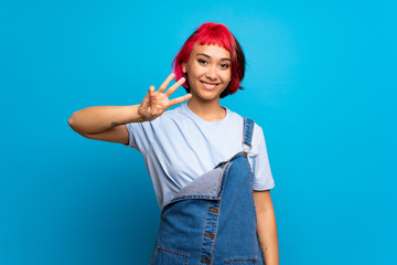 Young woman with pink hair over blue wall happy and counting three with fingers