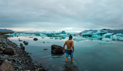 Young man enters the icy cold waters of Glacier lagoon. Man wearing only swimming shorts. Ice bergs drifting in the lagoon. Cold temperatures for ice swimming. Calm surface of the water