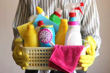 cleaning products in the basket in the hands of a young housewife.