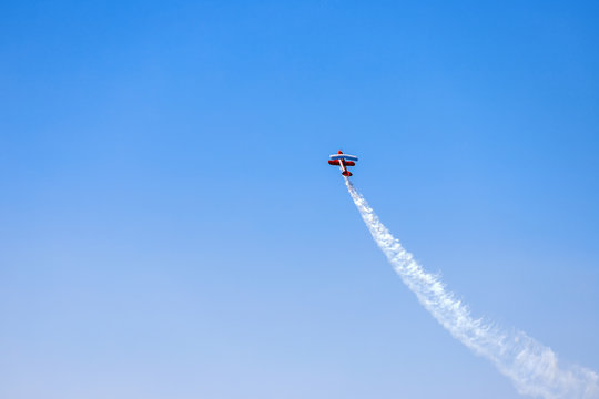 Stunt plane soars against blue sky background