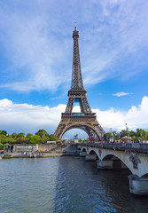 Eiffel Tower with view of Seine river and the bridge in cloudy blue sky day in Paris, France