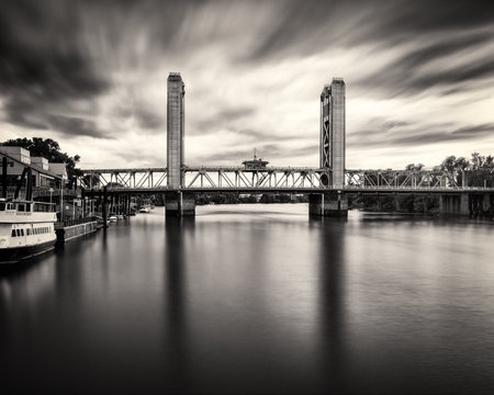 Dramatic black & white image of the Tower bridge with clouds streaking past.