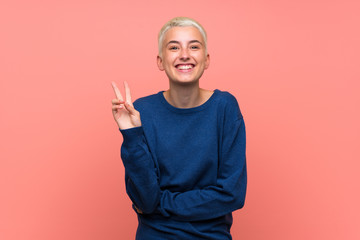 Teenager girl with white short hair over pink wall smiling and showing victory sign