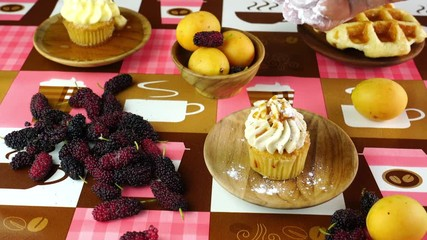 Fototapete - Hand sprinkling powder sugar on homemade cupcake in a wooden plate on a table with different kinds of fruit