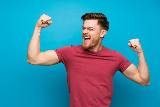 Redhead man on isolated blue wall celebrating a victory