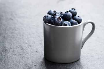 Cup full of fresh ripe blueberries on black stone background Wall mural