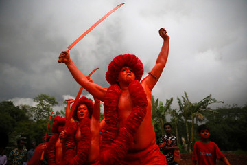 Hindu devotees join in a rally after applying colour on their body as they celebrate Lal Kach festival in Munshiganj