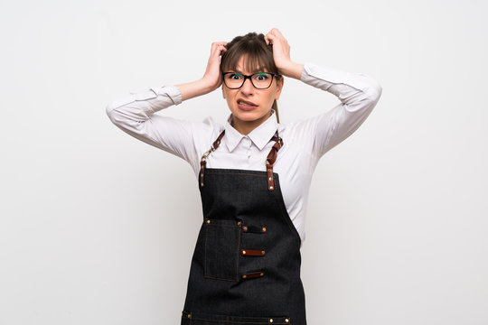 Young woman with apron frustrated and takes hands on head