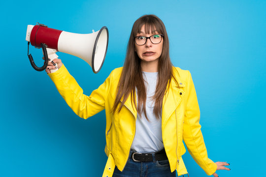 Young woman with yellow jacket on blue background taking a megaphone that makes a lot of noise