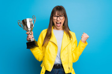 Young woman with yellow jacket on blue background holding a trophy Wall mural