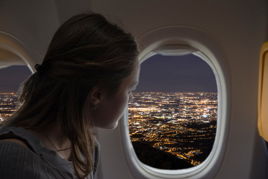 Woman looking out of the plane from the window during a night flight. City lights view