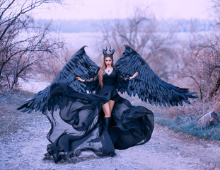 charming gorgeous dark witch controls wind, air flow waves hem and long train of light black dress with wide lace sleeves, lady with sharp horns and black feather wings ready to fly into sky