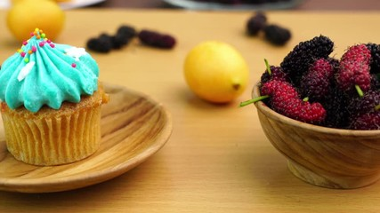 Fototapete - Dilicious Cupcake on a wooden plate with Mulberry and Marian plum in wooden bowl