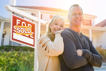 Attractive Middle-aged Couple In Front House and Sold Real Estate Sign