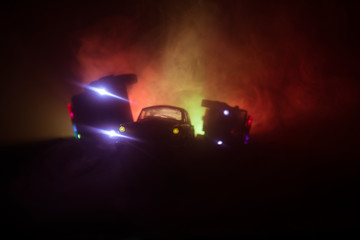 Fototapeta Police car chasing a car at night with fog background. 911 Emergency response police car speeding to scene of crime. Selective focus