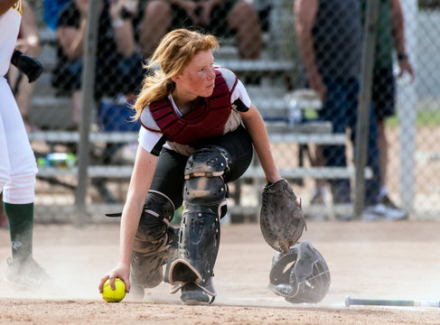 Skilled softbaall catcher with red hair and protective gear gaining a grip on the loose ball while looking up field.