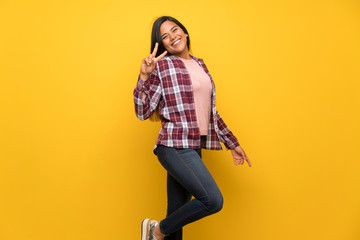 Young Colombian girl over yellow wall jumping