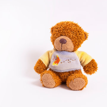 A small teddy bear in a yellow-blue sweater sits on a white background