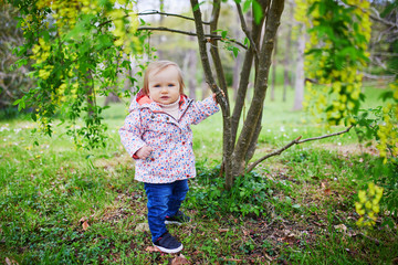 One year old girl standing next to a tree