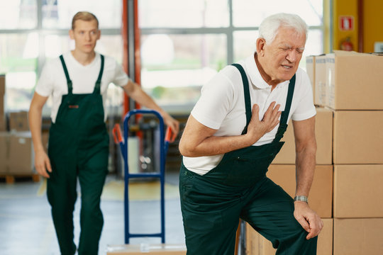 Senior warehouseman having a heart attack at work, young colleague running to help him