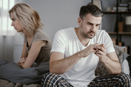 Man in pajamas sitting in bed and taking off his wedding ring after his wife announced that she wanted to get a divorce
