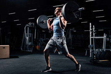 Athlete training with barbell in a gym - Functional, crossfit, workout concept
