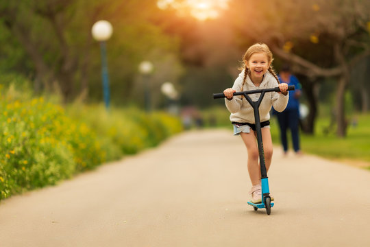 Portrait of active little toddler girl riding scooter on road in park outdoors on summer day. Seasonal child activity sport. Healthy childhood lifestyle