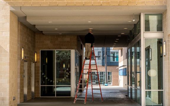 Worker on ladder changing light bulb