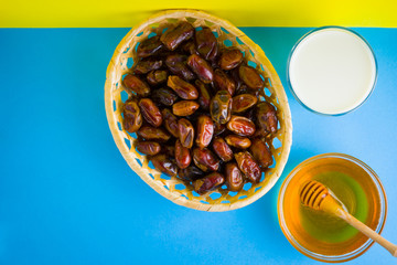 Dried dates, milk and honey on a yellow blue background. Holy month of Ramadan, concept. Righteous...