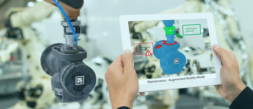 iot industry 4.0 concept,industrial engineer using smart tablet with augmented mixed with virtual reality technology to monitoring machine in real time.Smart factory use Automation robot arm