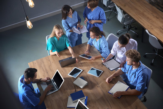 Group of medical students with gadgets in college, top view